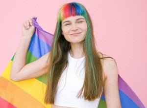 Eine junge Frau mit einer Regenbogenfahne